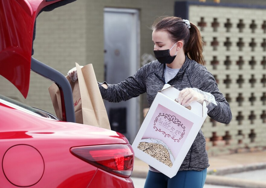 Volunteer Macy Sisson loads Passover supplies, including a Seder to go, into a trunk of a car at Chabad Center for Life and Learning in University City on April 6, 2020.