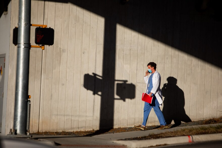 A medical professional walks outside Dell Seton Medical Center in Austin.