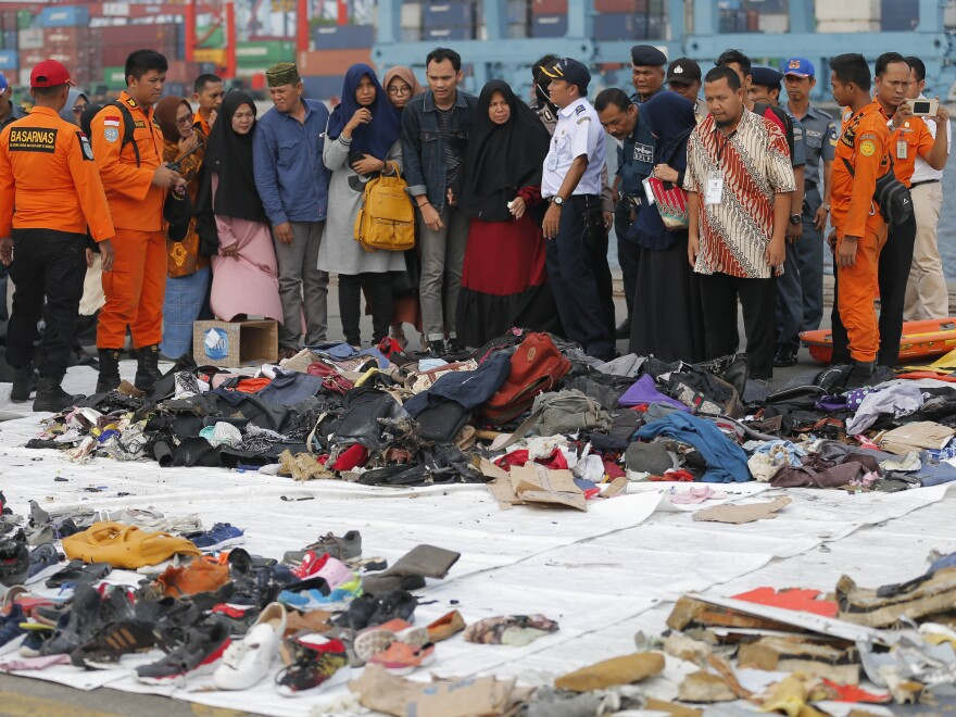 Relatives of passengers of the crashed Lion Air jet check personal belongings retrieved from the waters where the airplane crashed, at Tanjung Priok Port in Jakarta, Indonesia, last October.