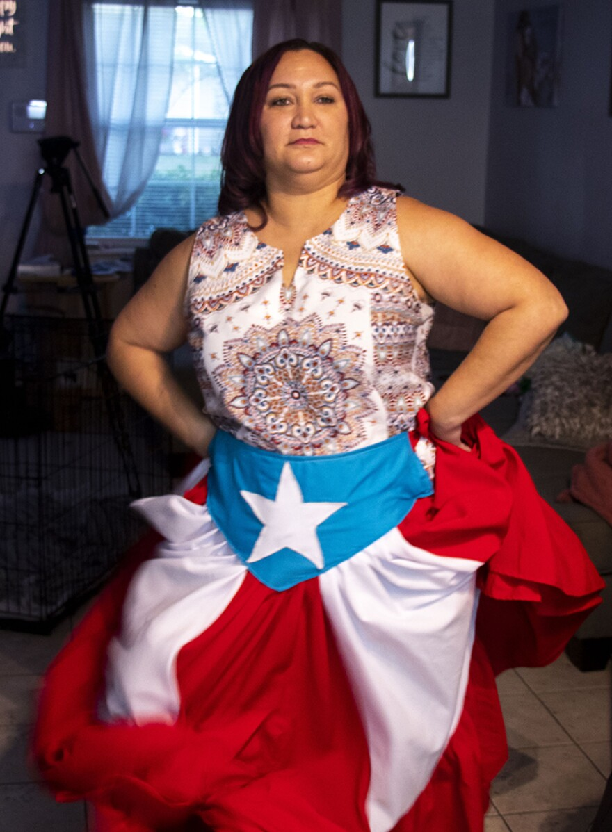 Barbara Liz-Cepeda wears a custom-tailored skirt with the Puerto Rican flag on it while she dances to the beat of the Bomba drums in her living room in Kissimmee, Fl.