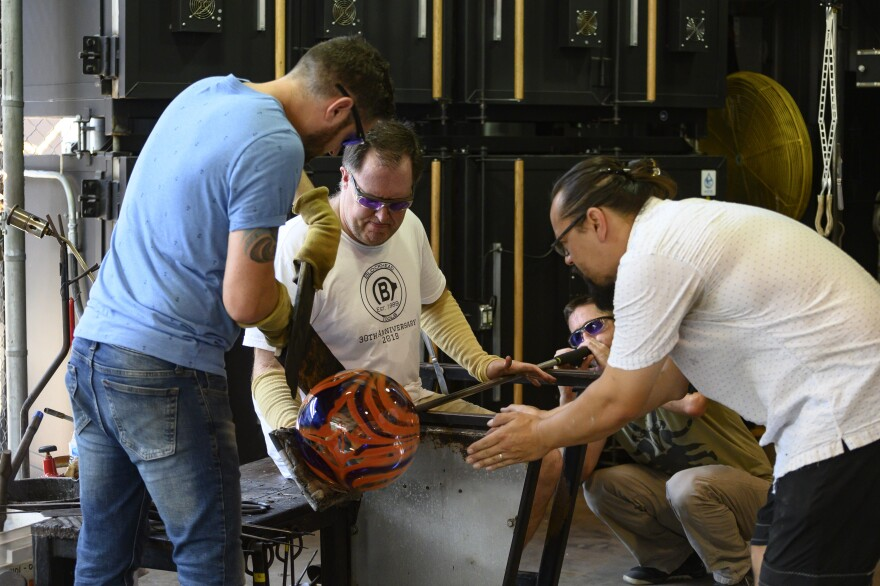 Glassblowing instructor Matthew Piepenbrock helps veterans create a piece in the Morean hot shop.