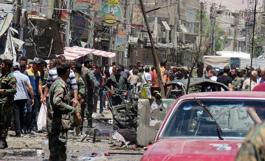 Syrian civilians and soldiers gather at the scene of a double bombing attack on Saturday outside the Sayyida Zeinab shrine, which is revered by Shiites around the world, some 6 miles south of the center of Damascus, state media said.