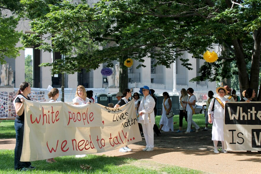 """A small group of Black Lives Matter activists carried banners reading """"White People, We Need to Talk"""" and """"White Silence is Violence"""" during the suffragette protest re-enactment Sat. Sept. 3, 2016."""