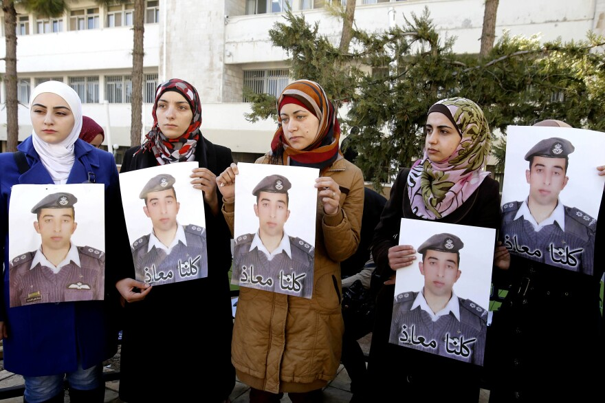 """Kaseasbeh's wife Anwar al-Tarawneh, center, holds a poster of him with Arabic that reads, """"We are all Muath,"""" during a rally in the Jordanian capital, Amman, on Tuesday."""