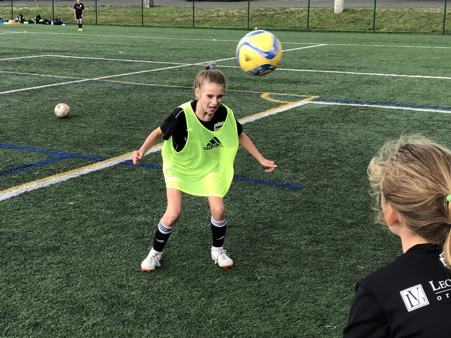 Eleven-year-old Ella Koehler, of Seattle United soccer club, heads the ball at a practice on the University of Washington campus. It's the first year she and her teammates of the same age can use the technique. A 2015 rule by the U.S. Soccer Federation banned heading for kids ages 10 years old and younger.