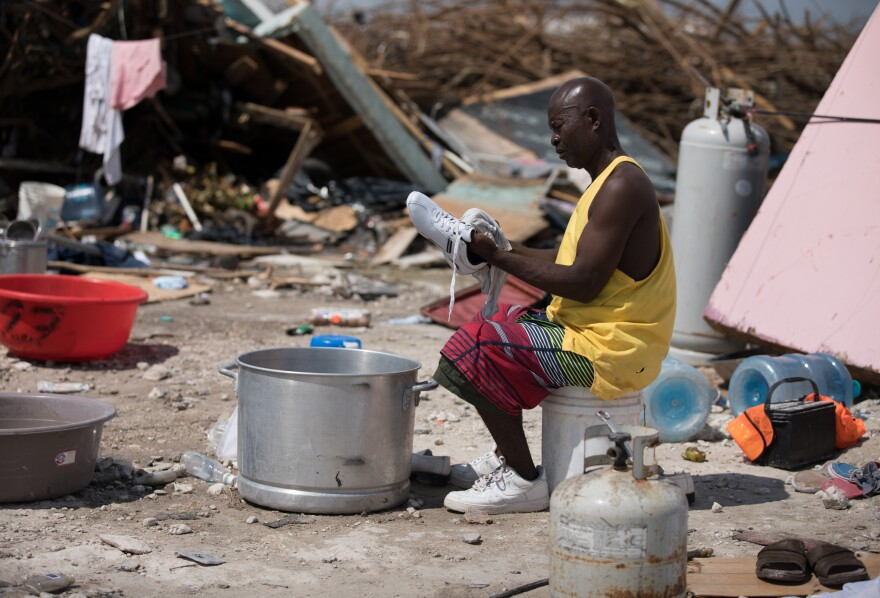 "Haitian Manes Lundy wipes off a pair of new shoes that he procured after all his belongings were destroyed. He lives in an area called The Mudd, home to about 8,000 Haitians. ""I have plenty of family dead here,"" Lundy said. ""That is the body of my cousin Doudoune Manes, but I don't have a way to bury her."""