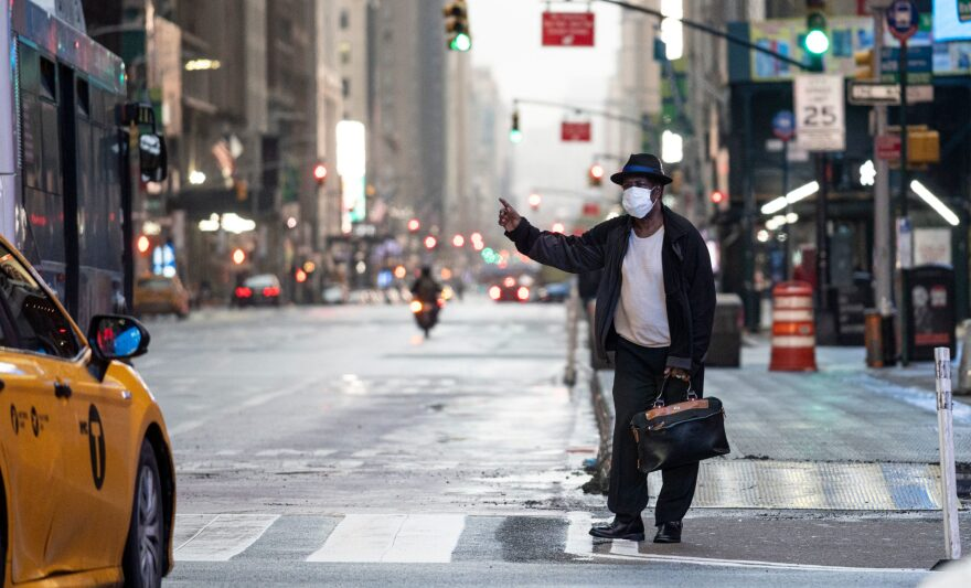 A man wearing a mask tries to catch a taxi at Times Square amid the Covid-19 pandemic on April 30, 2020 in New York City. (JOHANNES EISELE/AFP via Getty Images)