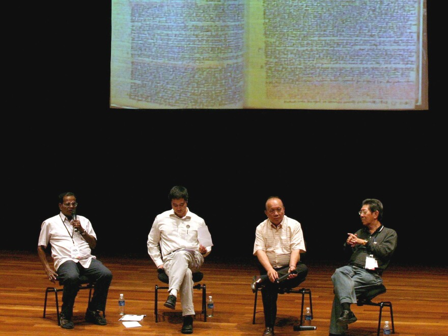 Former political detainees, Michael Fernandez (left), 72, and Tan Jing Quee (second from right), 66, participate in a forum in Singapore. A notebook used by Fernandez to scribble notes while he was jailed is projected behind them at the event held in 2006. Fernandez and Tan are among the hundreds of Singaporeans detained by the government without trial for, they say, political reasons.