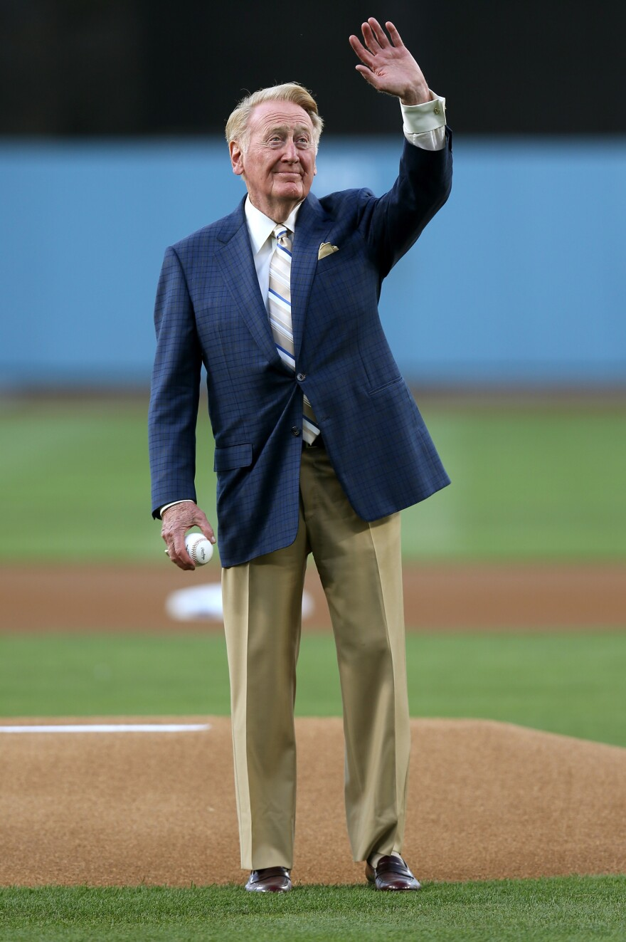 Legendary broadcaster Vin Scully has told the Los Angeles Dodgers that he'll return for his 65th year. Here, he waves to the crowd before throwing out the first pitch before a game last season.