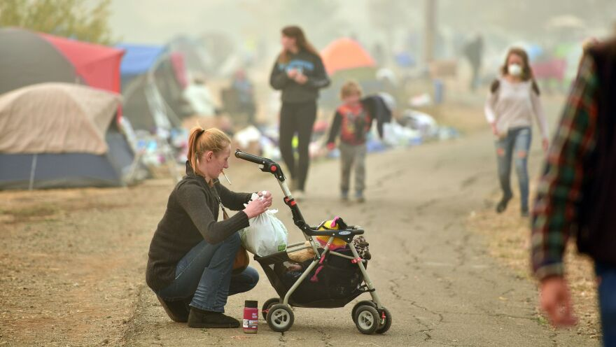 An evacuee tends to her baby Thursday at an encampment set up in a Walmart parking lot in Chico, Calif.