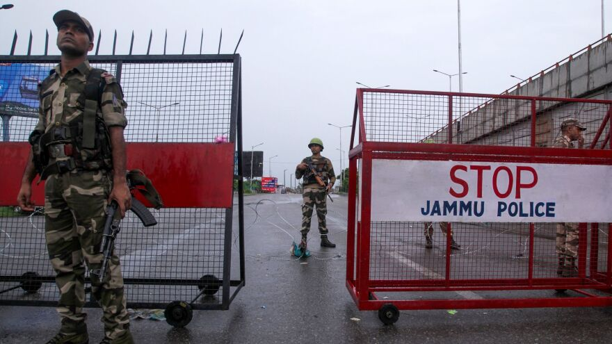 Security personnel stand guard at a roadblock in the city of Jammu on Tuesday.