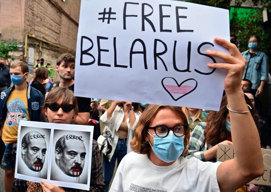 "A member of the Belarus diaspora holds a placard depicting Alexander Lukashenko with blood on his mouth and moustache past another with a placard reading ""#Free Belarus"" as they with others take part in a rally in support of Belarus people protesting vote rigging in the presidential election, outside the Belarusian embassy in Kiev."
