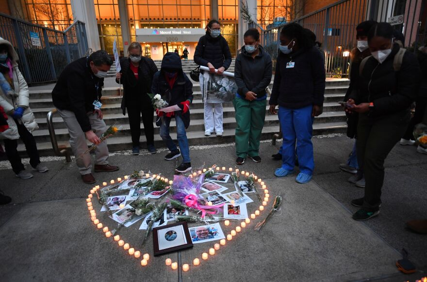 Nurses and health care workers light candles outside Manhattan's Mount Sinai Hospital on Friday as they mourn and remember their colleagues who died during the coronavirus pandemic.