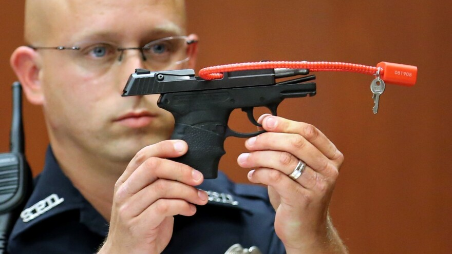 Sanford, Fla., police Officer Timothy Smith holds up the gun that was used to kill Trayvon Martin, while testifying on June 28, 2013, the 15th day of George Zimmerman's murder trial. Zimmerman has listed the gun for sale online.