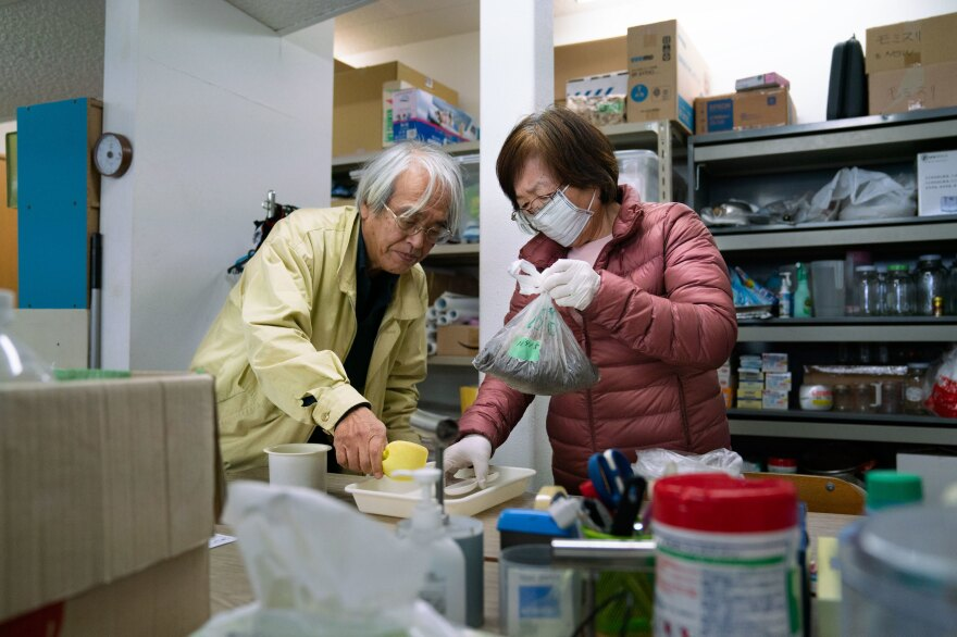 "Takenori Kobayashi (left) and his wife Tomoko Kobayashi bring soil samples into what they refer to as a ""grandma and grandpa lab"" to test it for radiation, in Fukushima prefecture, Japan."