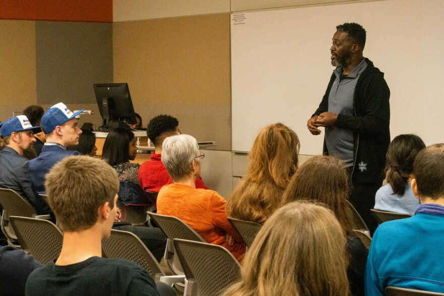 Picture of a man standing at the front of a classroom at Dixie State University addressing several rows of seated audience members.