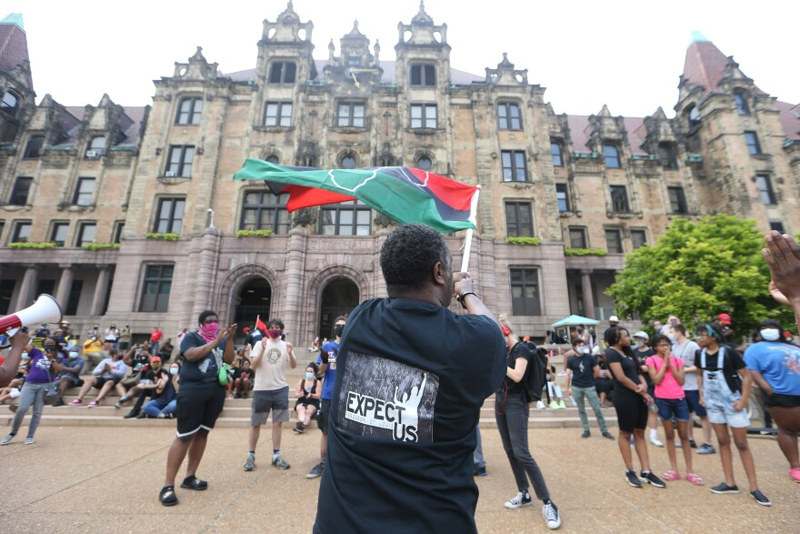 A Juneteenth organizer tries to pump up the crowd outside of St. Louis City Hall, by waving a flag on Friday, June 19, 2020.