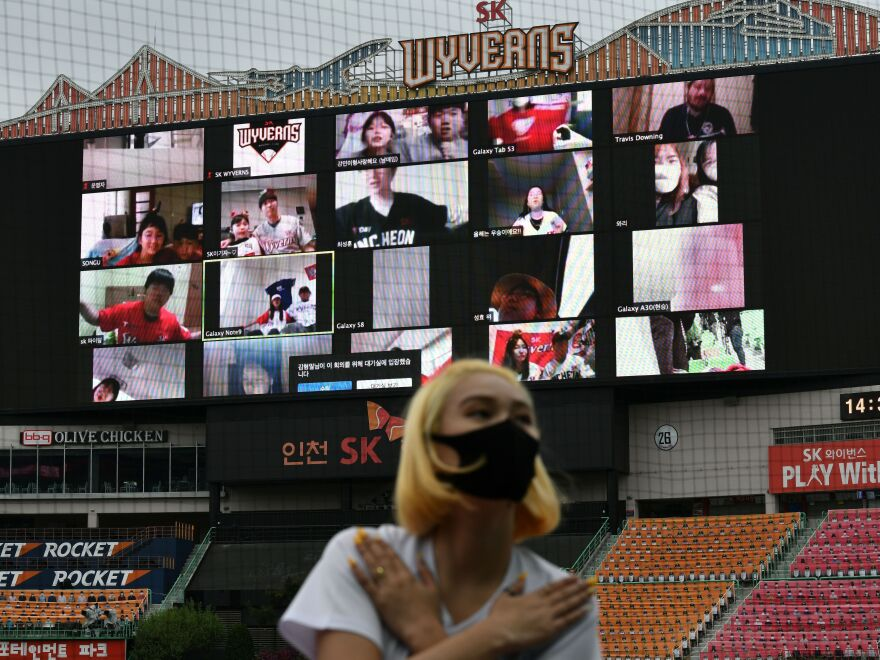 A cheerleader performs in front of a large screen displaying baseball fans cheering from their homes during the opening game of South Korea's new baseball season earlier this month.