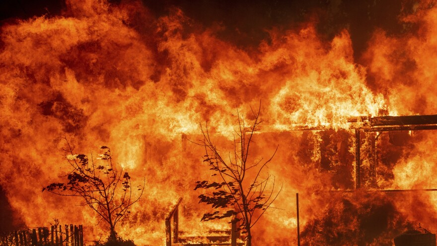 Flames consume a home as the River Fire tears though Lakeport, Calif., on Tuesday.