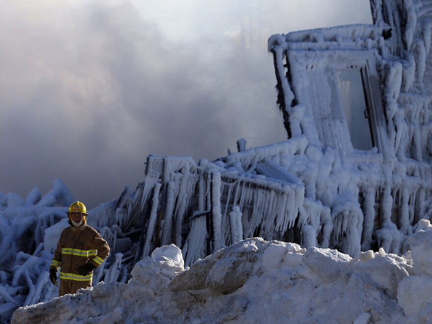 A firefighter walks past what is left of a seniors home in L'Isle Verte, Quebec. At least five people died and 30 are still missing after a fire there. The water used to fight the flames has frozen into ice that is a foot thick in places.