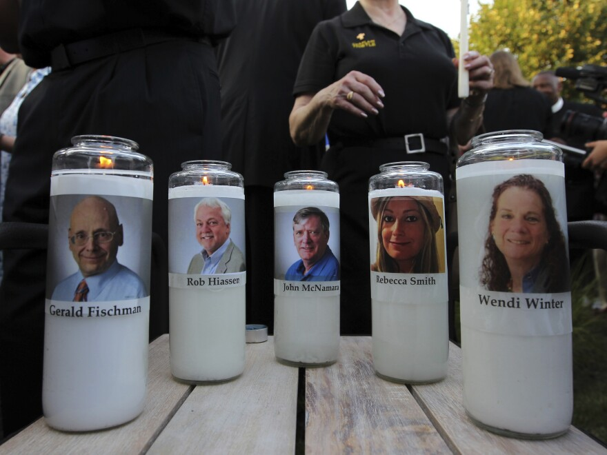 Photos of slain employees adorned candles at a vigil across the street from where they were killed in the newsroom.