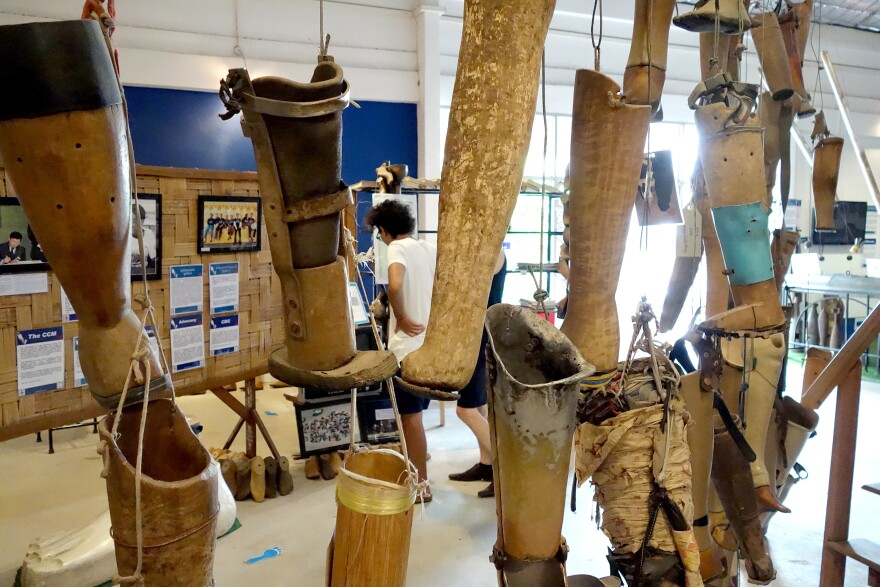 Homemade artificial limbs hang at the COPE Visitor Center. The Cooperative Orthotic and Prosthetic Enterprise is a nonprofit organization in Laos. The makeshift prosthetic legs, some of them clearly just rudimentary pieces of sanded wood, were donated by bombing survivors after use.