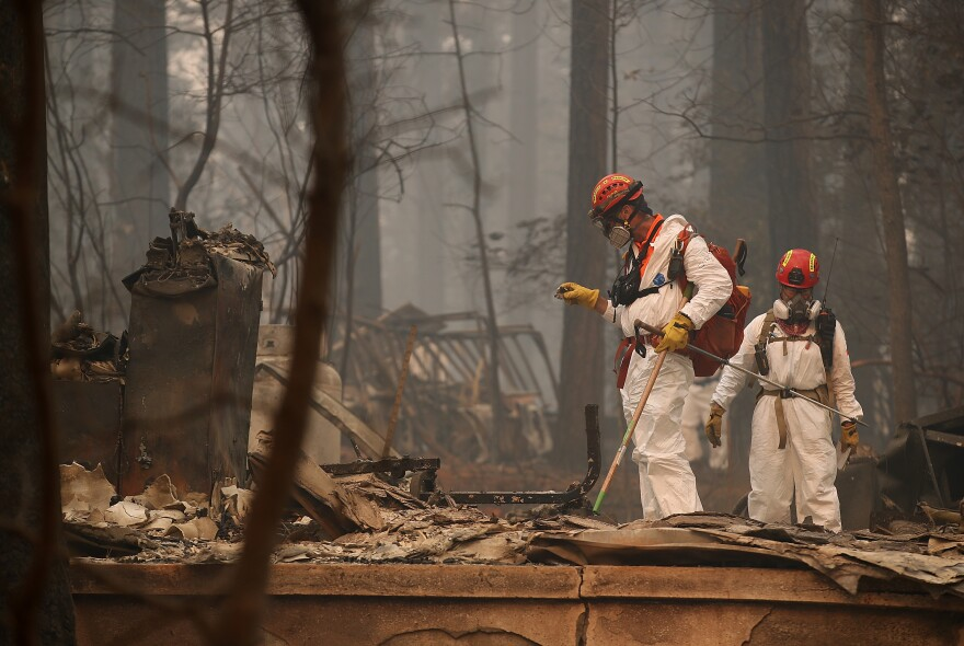 Rescue workers search for human remains on Thursday at a home that was burned by the Camp Fire in Paradise, Calif.