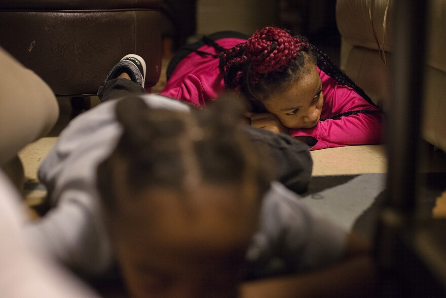 Khanyla Blueford, 12, and her siblings demonstrate a drill they practice in which they drop to the floor quickly at their home in East St. Louis. The drill helps them feel prepared for when they hear gunfire, which happens at least twice a week in warm mo