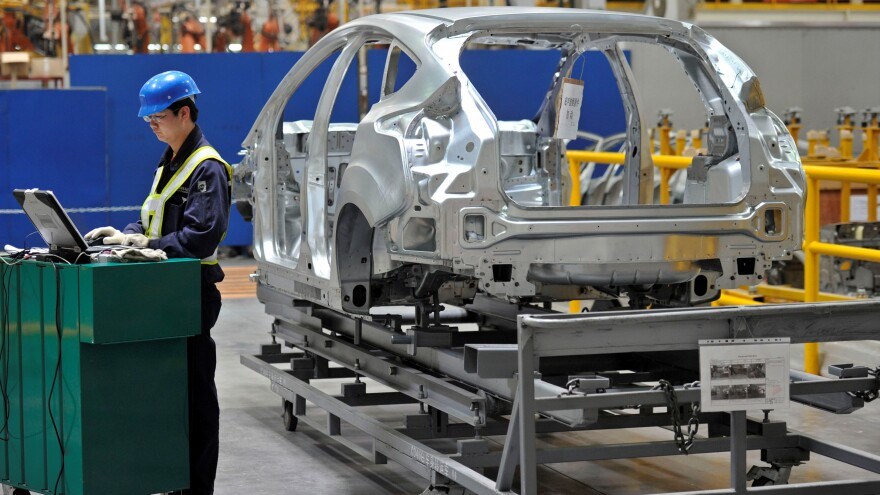 China's manufacturing sector helped boost the country's GDP, in statistics released on Thursday. Here, a worker at a Ford manufacturing plant uses a laptop next to a car body on an assembly line in Chongqing.