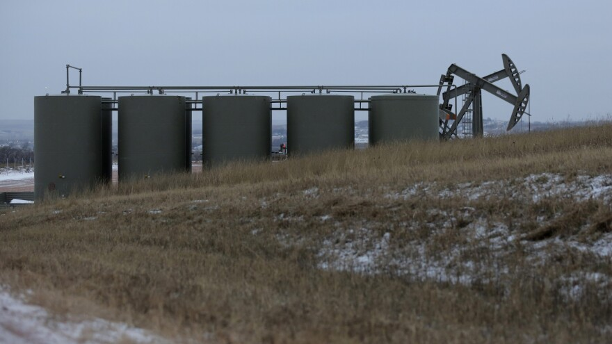 Oil pump jacks and storage tanks are seen Dec. 17 near Watford City, N.D. Oil prices are half what they were at the start of the year.