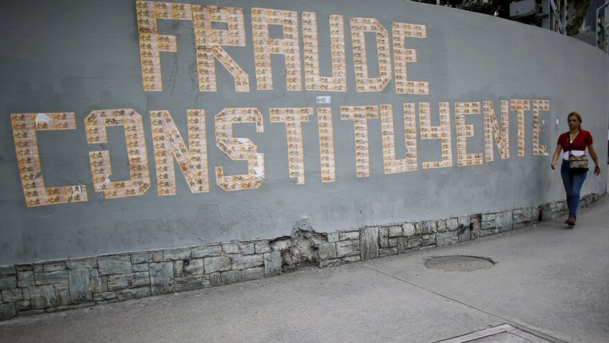 "A pedestrian walks next to a message on a wall formed with Venezuelan currency that reads in Spanish: ""The Constituent Assembly is a fraud"", in Caracas, Venezuela, on Monday."