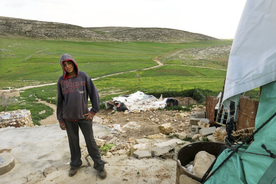 Majid Banifadel, 16, stands in the remains of his family home.