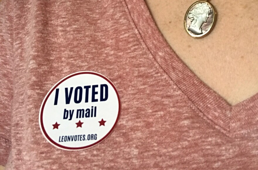 I Voted By Mail sticker on pink shirt