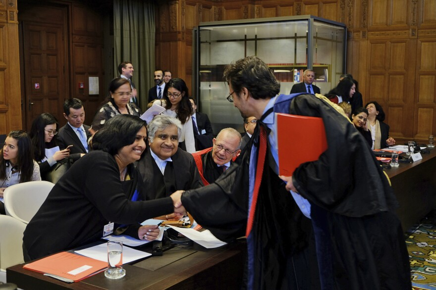 Members of the Indian delegation to the International Court of Justice, Neeru Chadha (left) and Harish Salve (center), greet a member of the Marshall Islands' legal team ahead of a preliminary hearing on nuclear disarmament at the International Court of Justice.