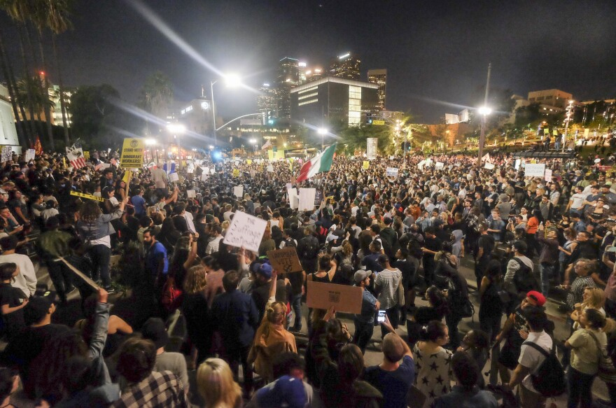 Demonstrators gather to protest a day after President-elect Donald Trump's victory, at a rally outside Los Angeles City Hall on Wednesday. Protesters burned a giant, orange-haired head of Donald Trump in effigy, lit fires in the streets and blocked traffic lanes late into the night.