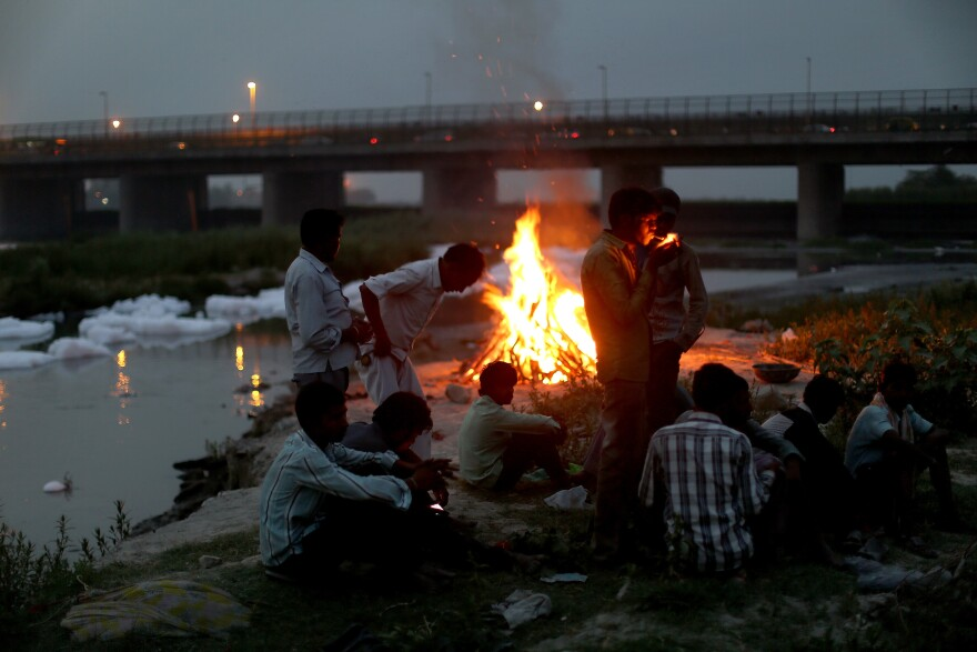 Men watch the fires of a cremation along the banks of the Yamuna River against the backdrop of the Wazirabad Barrage and floating industrial waste.