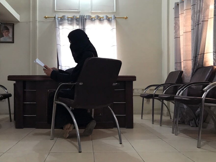 A friend of Nawaz Atta waits in a police station in Karachi to report his disappearance. She covers her face to avoid being identified.