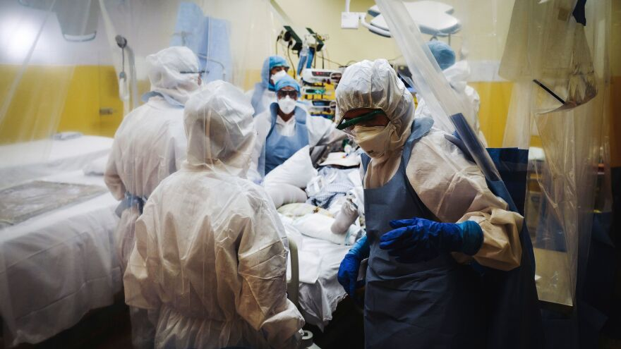 Medical staff, seen at a Paris hospital Thursday, treat a patient infected with COVID-19. The worldwide death toll connected with the disease topped 100,000 on Friday — a startling statistic that may have seemed unthinkable just several months ago.