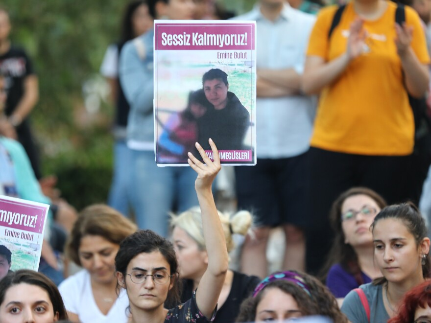 """Women protest against women's murders in Ankara, Turkey, on Aug. 23. Signs say """"We are not silent"""" and show Emine Bulut, whose killing by her ex-husband was captured on video that was widely shared on social media."""