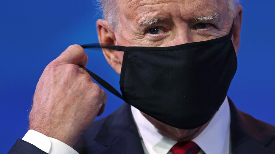 President-elect Joe Biden takes off his mask before laying out his proposal for a $1.9 trillion coronavirus relief package on Jan. 14.