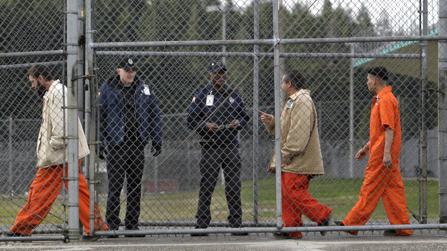 Inmates walk past correctional officers at the Washington Corrections Center in Shelton, Wash., in 2011. Gov. Jay Inslee said Tuesday that more than 3,000 prisoners in Washington have been mistakenly released early since 2002 because of an error by the state's Department of Corrections.