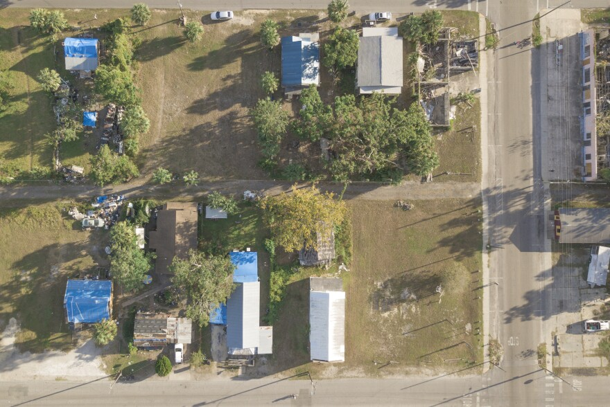 Photo from above showing roofs with blue tarps and even some buildings with roofs missing