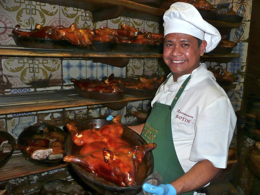 Roel Basalm Alim, a cook at Restaurante Botín, displays a plate of <em>cochinillo asado</em>, or roast suckling pig.