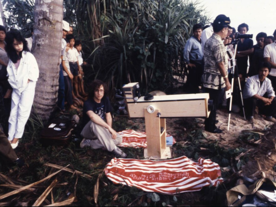 """Astronomer Glenn Schneider (center) was on the coast of Bangka Island, Indonesia, on March 18, 1988, preparing to observe and photograph that day's total solar eclipse using his """"disposable"""" telescopic eclipse camera."""