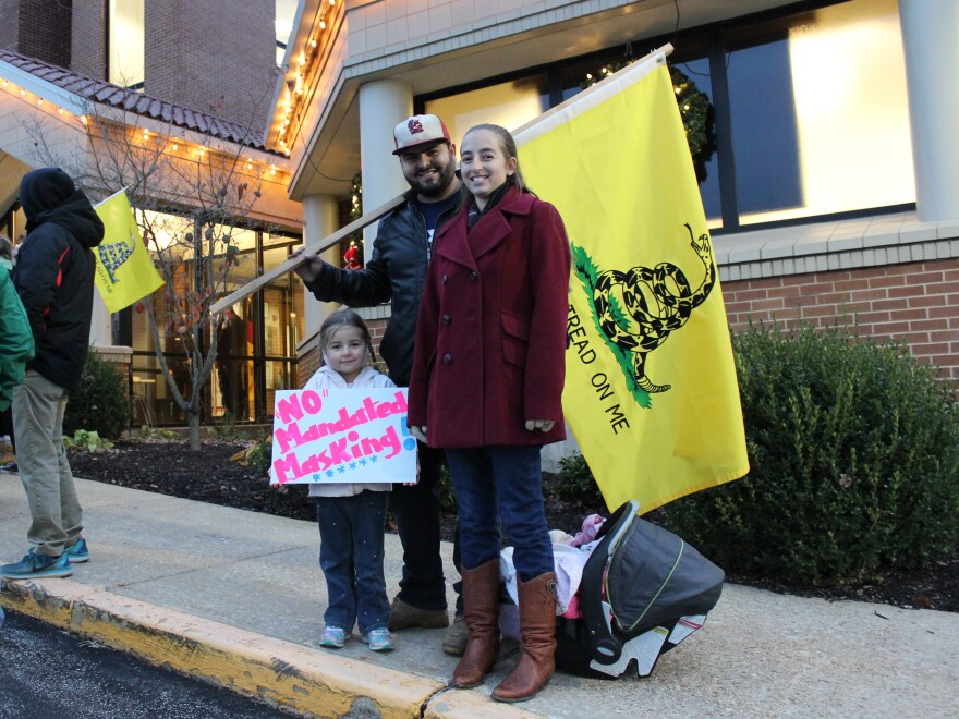 "Outside City Hall on the evening of a vote on a proposed mask order in Washington, Mo., residents Ali and Duncan Whittington protest against the order, along with their 4-year-old daughter. ""I'm here because I feel my freedom is being violated,"" Ali says."