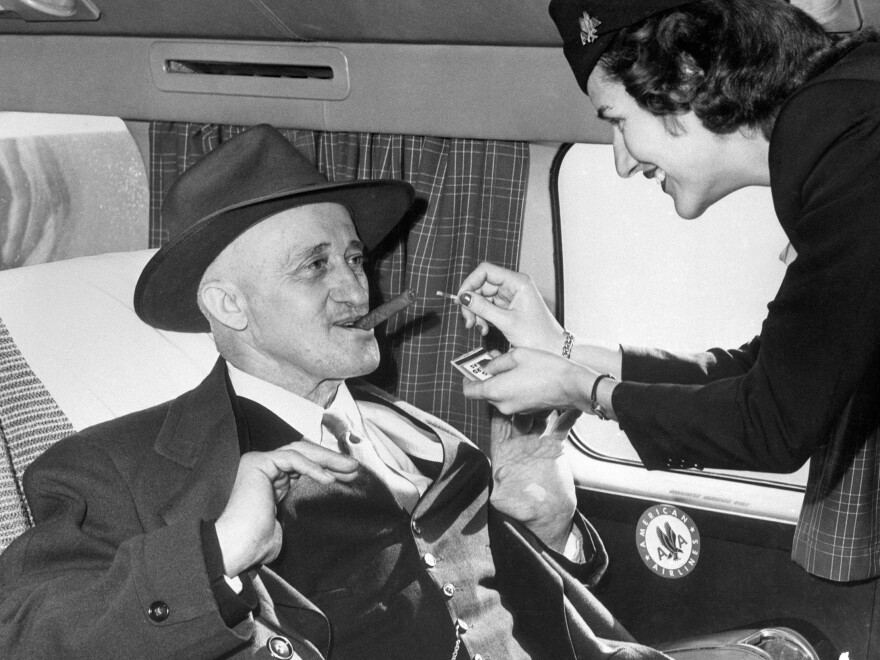 Those were the days: A stewardess lights a cigar for a  passenger aboard an American Airlines flight in 1949.