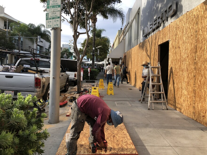 Workers board up a business in Beverly Hills, Calif., last weekend.