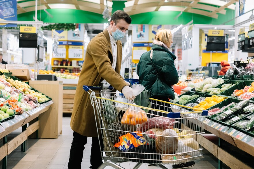 A man in a medical mask buys food at a grocery store.