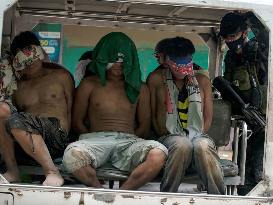 Suspected militants are borne away blindfolded in a police vehicle on the outskirts of Marawi on Saturday.