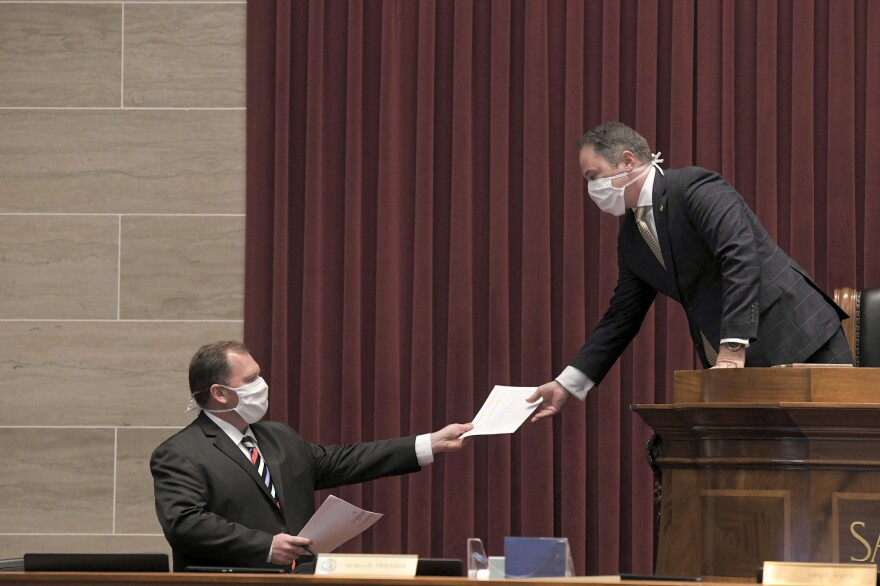 House Speaker Elijah Haahr, right, hands some papers to House Majority Leader Rob Vescovo earlier this month in Jefferson City.